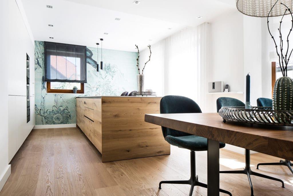 Mit Holz und gedeckten Unifarben lässt sich Wandfarbe in der Küche ideal integrieren. (Foto: Dross&Schaffer Ingolstadt)