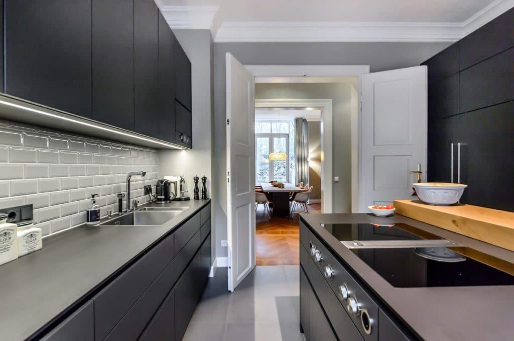 Eine graue Wandfarbe in der Küche schafft den sanften Übergang zwischen schwarzen Fronten und weißen Türen. (Foto: Dross&Schaffer Küchen)