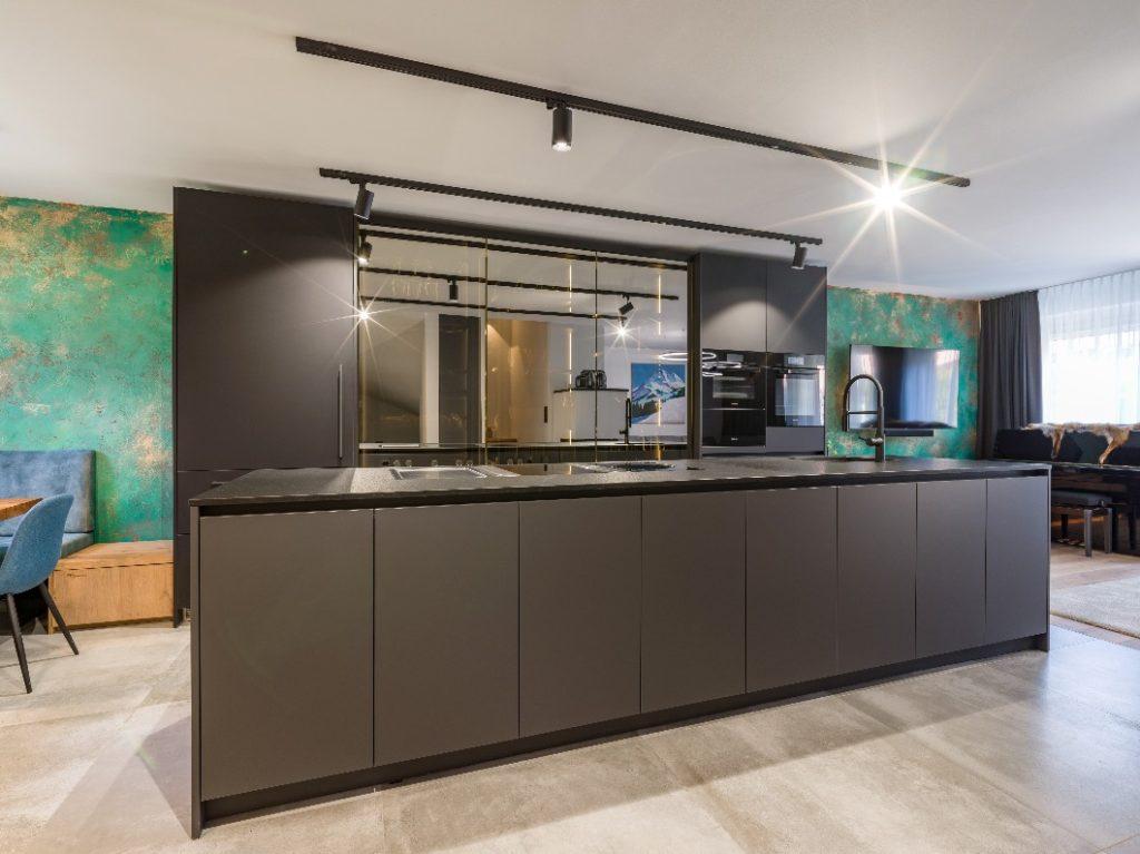 Opulenter Kontrast zur geradlinigen, schwarzen Küche: die handgespachtelte Wandgestaltung von Kunstmaler Akram Sultan aus Augsburg. (Foto: The Kitchen Club)